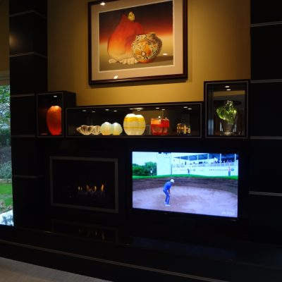 The firebox saves energy by adding supplemental heat and is controlled by a hand-held device. LEDs accent the art glass.